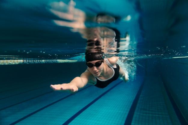 Atleta nadando debaixo d'água com óculos de proteção