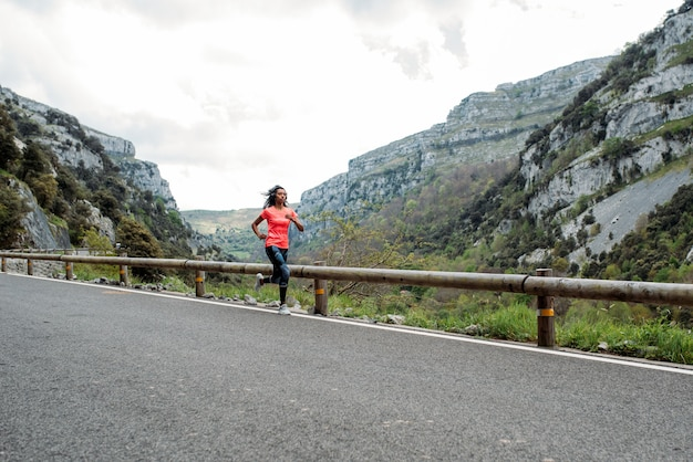 Atleta negra em roupas esportivas, correndo em rota pavimentada com cerca contra vale de montanha de paisagem