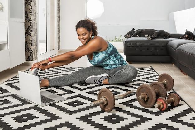 Atleta negra sorridente, esticando as pernas e assistindo o vídeo tutorial no laptop, enquanto aquece os músculos durante o treinamento em casa