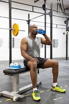 Atleta negro bebendo água após treino no ginásio. esporte e estilo de vida saudável.