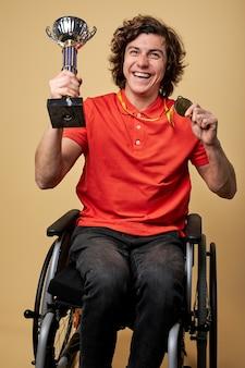Atleta paralímpico com deficiência física em cadeira de rodas segurando taça de campeão e medalhas de ouro isoladas em parede bege