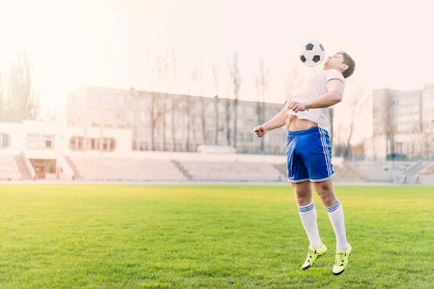 Atleta pegando bola de futebol com peito