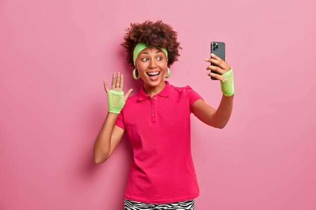 Atleta positiva em uso ativo acena com a mão para a câmera do smartphone, tira selfie, envia foto aos seguidores, tem bom humor, faz gesto de saudação, sorri na tela do celular