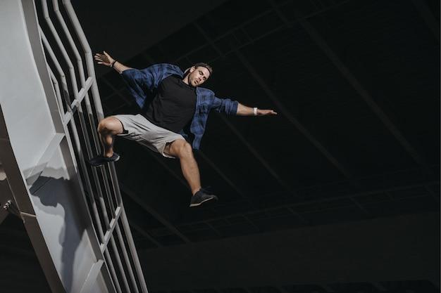 Atleta praticando freerunning fazendo um grande salto assustador. parkour gosta de estilo de vida