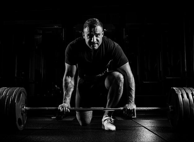 Atleta profissional curvado sobre a barra e se preparando para levantar um peso muito grande. vista frontal