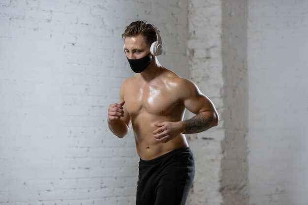 Atleta profissional do sexo masculino treinando em fundo de parede de tijolos usando máscara facial