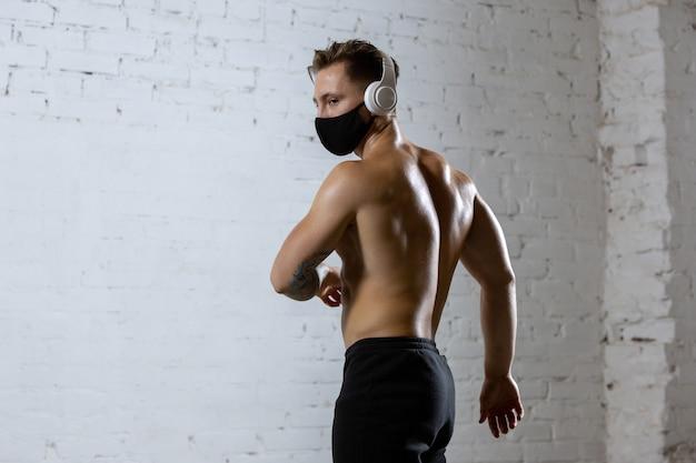 Atleta profissional do sexo masculino treinando no fundo da parede de tijolos, usando máscara facial.