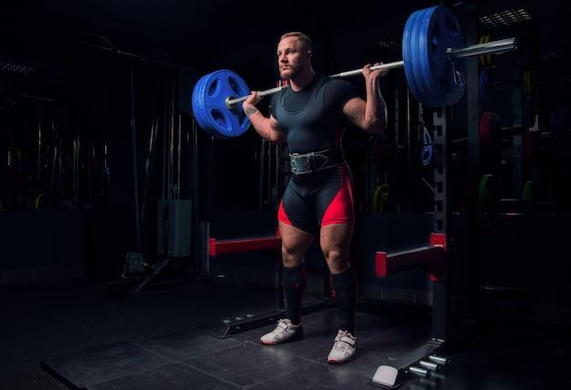 Atleta profissional faz agachamento com barra na academia