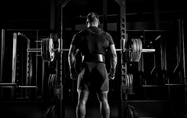 Atleta profissional fica em frente às barras com uma barra e está prestes a se agachar com ela. vista traseira