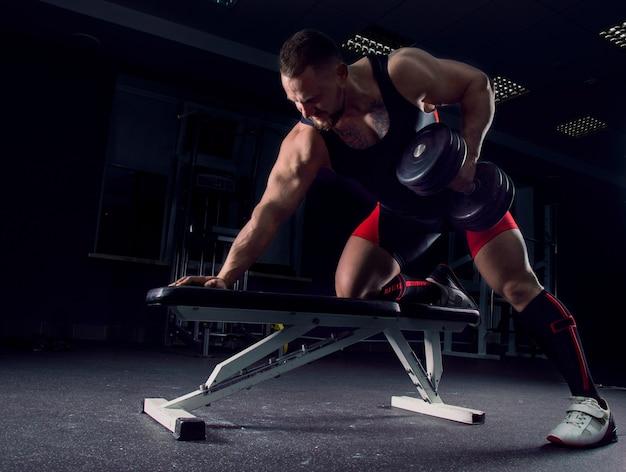 Atleta profissional na academia puxa os halteres até o estômago