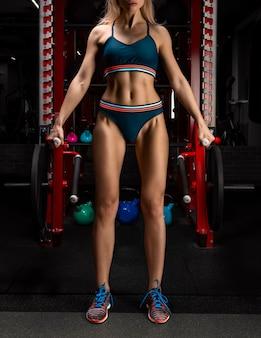 Atleta profissional realiza exercícios de levantamento terra. o conceito de esportes, academias, roupas esportivas, fitness. preparando-se para a competição. figura ideal. mídia mista