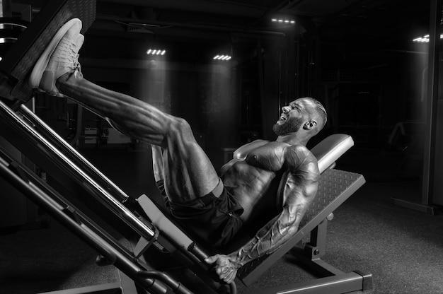 Atleta profissional realiza um exercício de perna. conceito de musculação, fitness, esportes. mídia mista