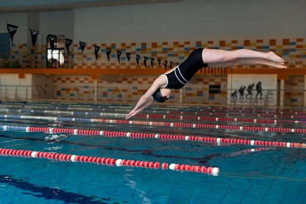 Atleta pulando na piscina tacada completa