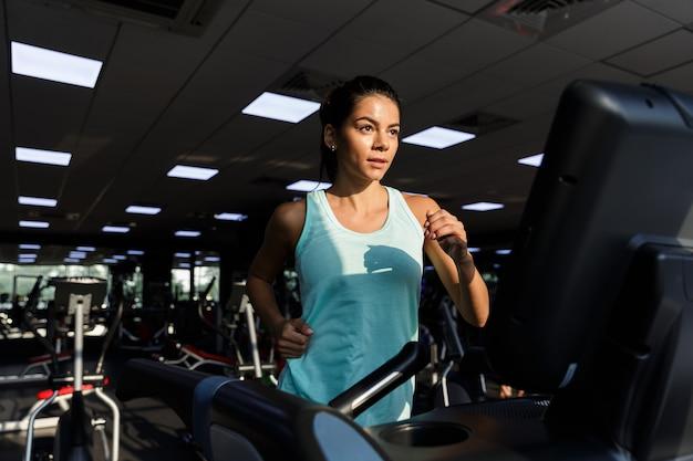Atleta satisfeita fazendo exercícios de fitness e desviando o olhar na academia