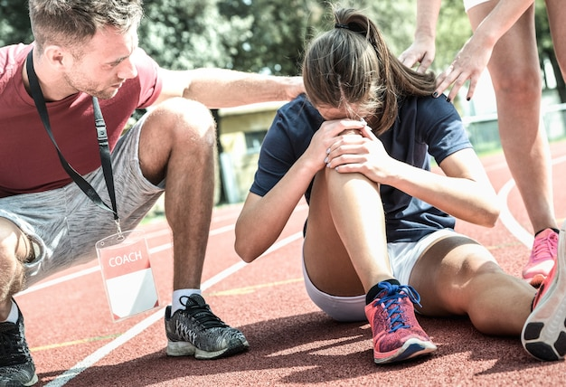 Atleta se machucando durante o treinamento de corrida atlética
