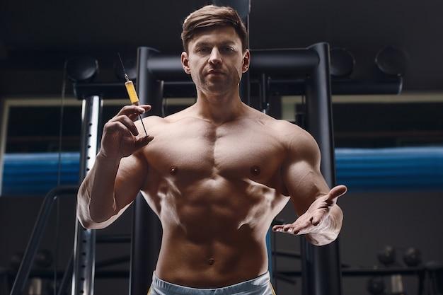 Atleta segura uma seringa, injetor na frente dele com o torso nu. conceito de medicina esportiva e vacinação