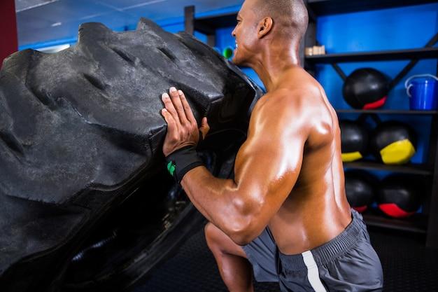 Atleta sem camisa, empurrando o pneu