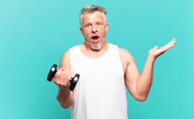 Atleta sênior parecendo surpreso e chocado, com o queixo caído segurando um objeto com a mão aberta na lateral