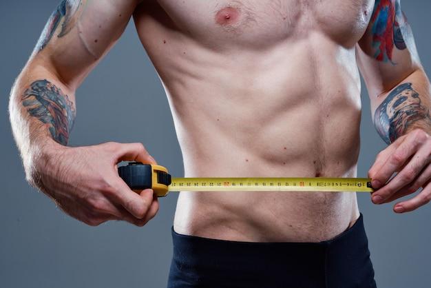 Atleta sexy com músculos do braço fortalecidos e fisiculturista com fita centímetro