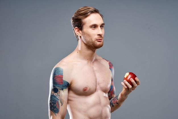 Atleta sexy com músculos para cima come uma maçã em um cinza e uma tatuagem no braço