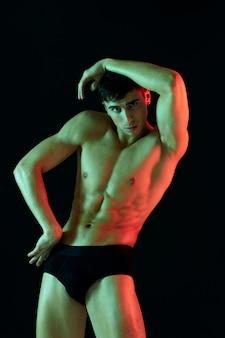 Atleta sexy com um torso forte mantém a mão acima da cabeça em um fundo preto