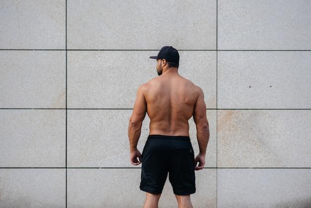 Atleta sexy fica de costas contra a parede. ginástica. estilo de vida saudável.