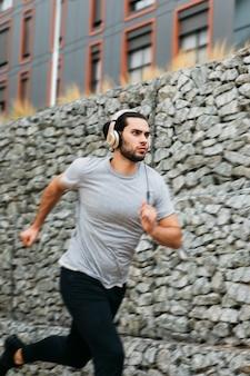Atleta urbana ao lado da parede de pedra