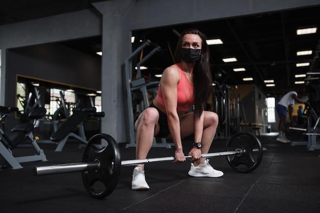 Atleta usando máscara médica fazendo agachamentos de sumô com barra