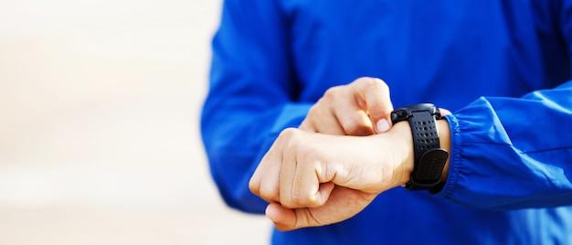 Atleta verificando seu cronômetro de corrida de relógio de pulso correndo pronto no campo de prática ao ar livre.