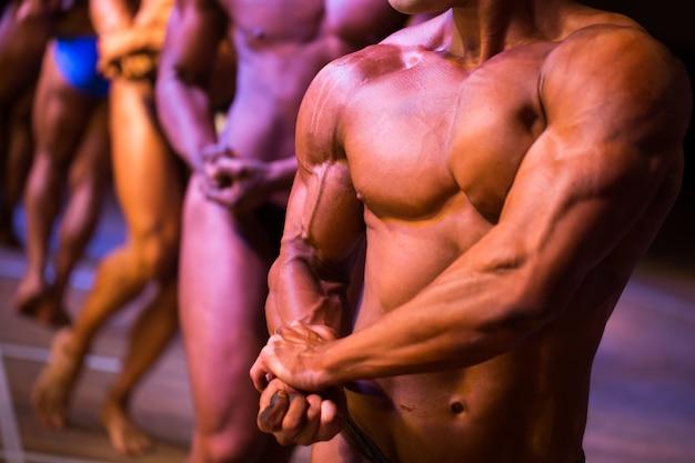 Atletas bodybuilders estão esticando o lado do bíceps do braço