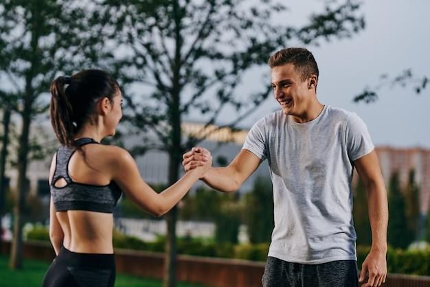 Atletas de homem e mulher correndo na natureza no parque