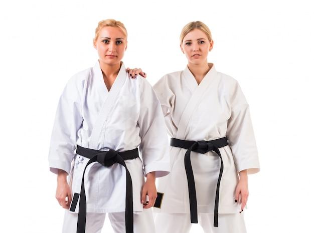 Atletas de meninas no quimono de karatê com cintos pretos