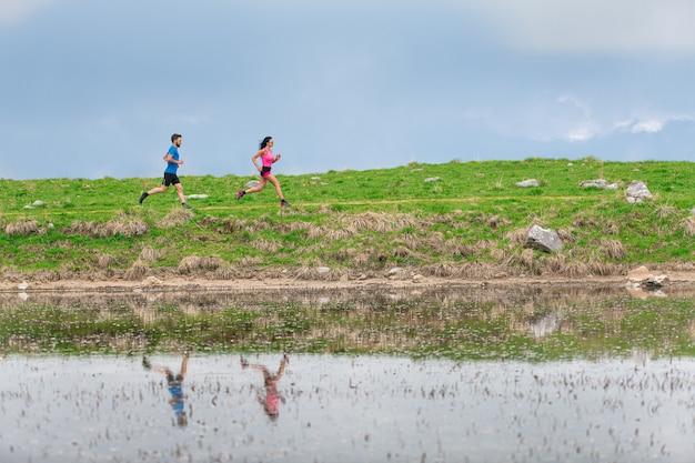 Atletas em treinamento nas montanhas são refletidos no lago enquanto correm