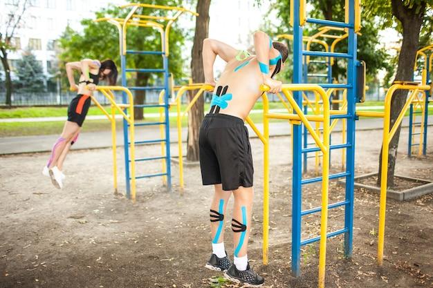 Atletas emparelhados com faixas elásticas cinesiológicas em corpos em um campo esportivo