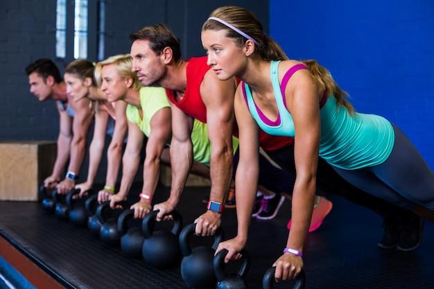 Atletas exercitando com kettlebells