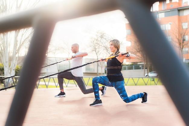 Atletas fazendo exercícios com um bastão de ginástica elástico no parque