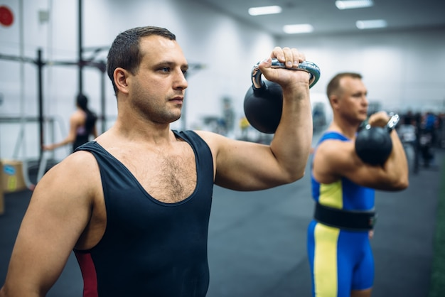 Atletas fortes do sexo masculino com pesos na academia