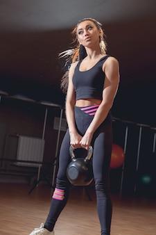 Atletas jovens saudáveis fazendo exercícios com kettlebells, no estúdio de fitness