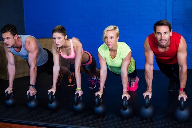 Atletas masculinos e femininos, exercitando com kettlebells