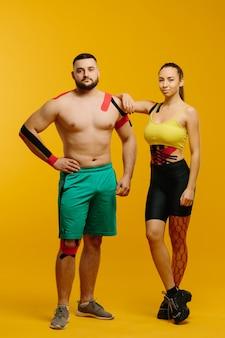 Atletas profissionais, homem e mulher com fita cinesiológica no corpo, posando em amarelo