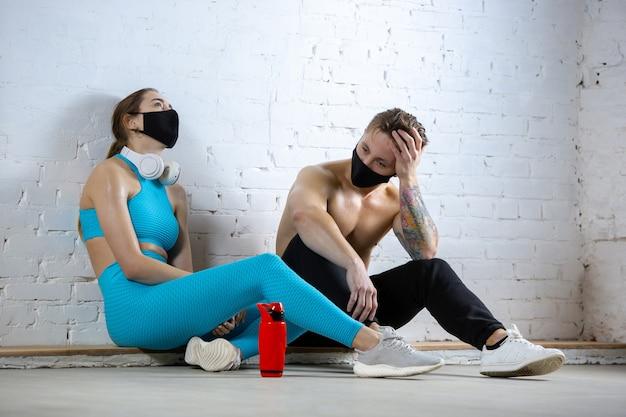 Atletas profissionais treinando em fundo de parede de tijolos usando máscara facial. esporte durante quarentena