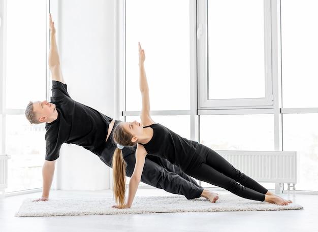 Atletas realizando exercícios de prancha lateral