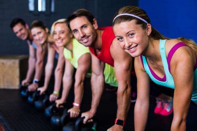 Atletas sorridentes exercitando com kettlebells