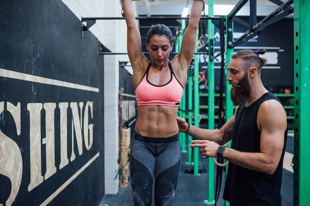 Atletic jovem fazendo puxar para cima no bar de ginástica, ajudado por personal trainer
