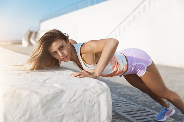 Atlética bonita, ambiciosa, motivada e vestindo shorts fazendo flexões