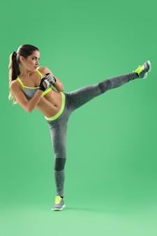 Atlética desportista treinamento lado chute no studio sobre fundo verde
