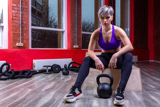 Atlética e feliz jovem loira feminina posando com halteres em uma academia.