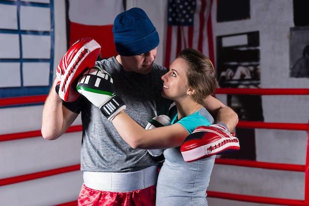 Atlética feminina abraça o namorado boxeador em um ringue de boxe normal em uma academia