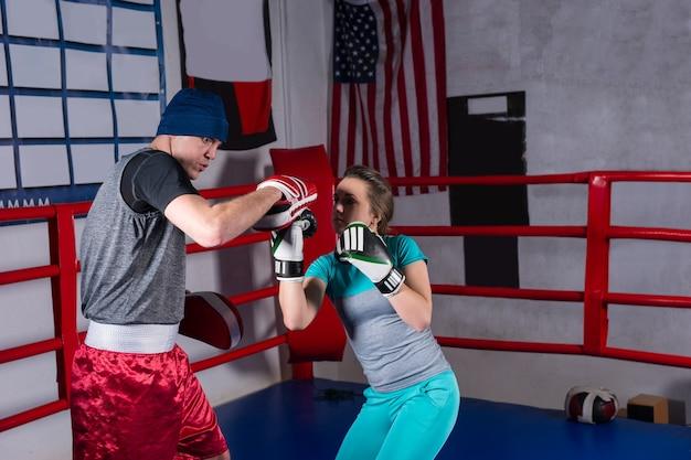 Atlética feminina fazendo treinamento de kickboxing com o técnico em um ringue de boxe normal em uma academia