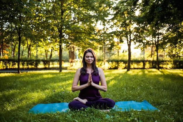 Atlética garota com os olhos fechados, sentado no tapete de ioga em uma pose de namaste na natureza ao pôr do sol
